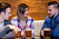 Amis heureux avec des tasses de bière dans le restaurant Image stock