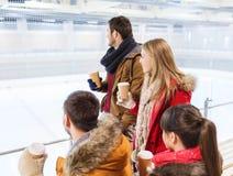 Amis heureux avec des tasses de café sur la piste de patinage Image stock