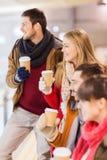 Amis heureux avec des tasses de café sur la piste de patinage Photographie stock libre de droits