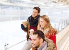 Amis heureux avec des tasses de café sur la piste de patinage Images libres de droits