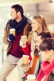 Amis heureux avec des tasses de café sur la piste de patinage Photos stock