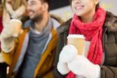Amis heureux avec des tasses de café sur la piste de patinage Photo stock