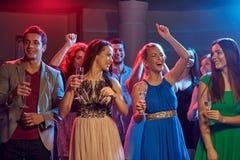Amis heureux avec des verres de champagne dans le club Images stock