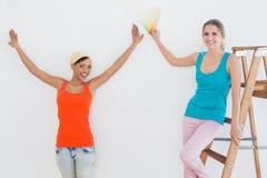 Amis heureux avec l'échelle choisissant la couleur pour peindre une salle Photo libre de droits