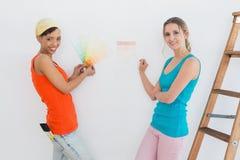 Amis heureux avec l'échelle choisissant la couleur pour peindre une salle Images libres de droits