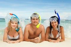Amis avec l'équipement naviguant au schnorchel sur la plage Photographie stock libre de droits