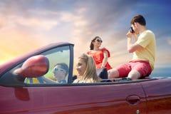 Amis heureux avec l'appareil-photo conduisant dans la voiture Image stock