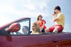 Amis heureux avec l'appareil-photo conduisant dans la voiture de cabriolet Image libre de droits