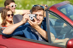 Amis heureux avec l'appareil-photo conduisant dans la voiture de cabriolet Photos libres de droits