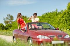 Amis heureux avec l'appareil-photo conduisant dans la voiture de cabriolet Photo stock