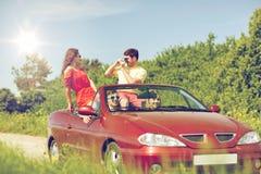 Amis heureux avec l'appareil-photo conduisant dans la voiture de cabriolet Images libres de droits