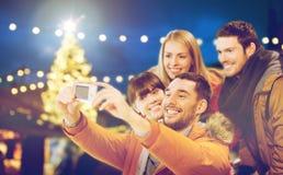 Amis heureux avec l'appareil-photo prenant le selfie de Noël Photos libres de droits