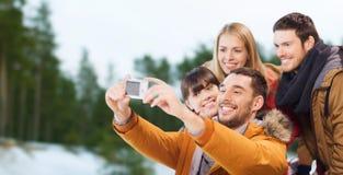 Amis heureux avec l'appareil-photo sur la piste de patinage Image stock