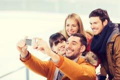 Amis heureux avec l'appareil-photo sur la piste de patinage Image libre de droits