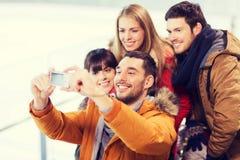 Amis heureux avec l'appareil-photo sur la piste de patinage Photo stock