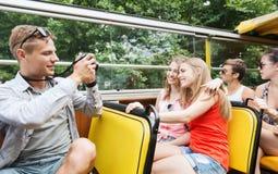 Amis heureux avec l'appareil-photo voyageant en bus touristique Photo stock