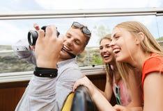 Amis heureux avec l'appareil-photo voyageant en bus touristique Photo libre de droits