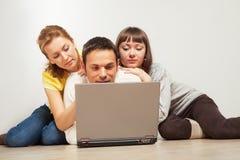 Amis heureux avec l'ordinateur portable Photos stock