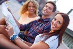 Amis heureux avec la carte Photos stock