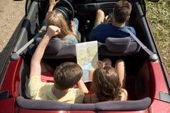 Amis heureux avec la carte conduisant dans la voiture convertible Photos libres de droits