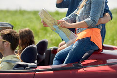Amis heureux avec la carte conduisant dans la voiture convertible Photos stock