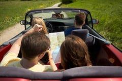 Amis heureux avec la carte conduisant dans la voiture convertible Photo libre de droits