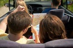 Amis heureux avec la carte conduisant dans la voiture convertible Image stock