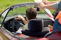 Amis heureux avec la carte conduisant dans la voiture convertible Photographie stock libre de droits