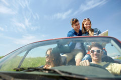 Amis heureux avec la carte conduisant dans la voiture de cabriolet Photo stock