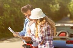 Amis heureux avec la carte conduisant dans la voiture de cabriolet au pays et indiquant le doigt quelque chose en avant Photos libres de droits