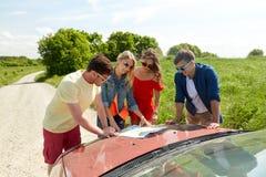 Amis heureux avec la carte et la voiture à la route de campagne Photographie stock