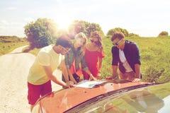 Amis heureux avec la carte et la voiture à la route de campagne Photos libres de droits