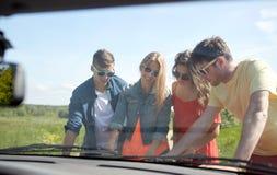 Amis heureux avec la carte et la voiture recherchant l'emplacement Photo stock
