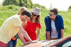 Amis heureux avec la carte et la voiture recherchant l'emplacement Images libres de droits