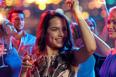 Amis heureux avec la danse de champagne à la boîte de nuit Photo stock