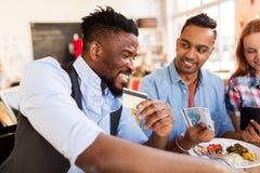 Amis heureux avec la facture de paiement d'argent au restaurant Photo stock