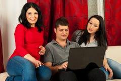 Amis heureux avec la maison d'ordinateur portatif Photos stock