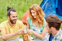 Amis heureux avec la tente et boissons au terrain de camping Image stock