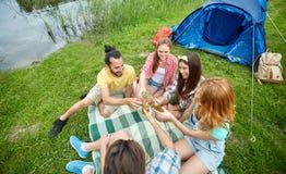 Amis heureux avec la tente et boissons au terrain de camping Photos libres de droits