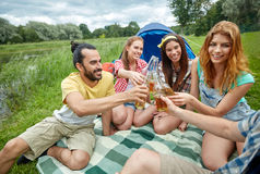 Amis heureux avec la tente et boissons au terrain de camping Photographie stock libre de droits