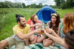 Amis heureux avec la tente et boissons au terrain de camping Photographie stock