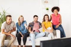 Amis heureux avec la TV de observation à distance à la maison Photographie stock