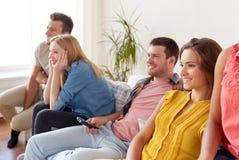 Amis heureux avec la TV de observation à distance à la maison Images stock