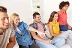 Amis heureux avec la TV de observation à distance à la maison Photo stock