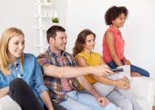 Amis heureux avec la TV de observation à distance à la maison Image stock