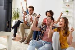 Amis heureux avec la TV de observation à distance à la maison Photos libres de droits