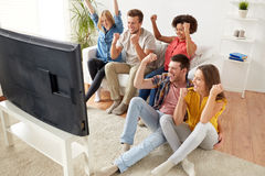 Amis heureux avec la TV de observation à distance à la maison Image libre de droits