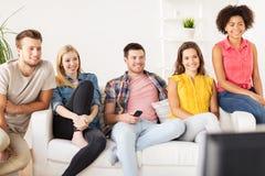 Amis heureux avec la TV de observation à distance à la maison Images libres de droits