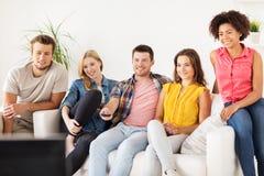 Amis heureux avec la TV de observation à distance à la maison Photographie stock libre de droits