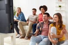Amis heureux avec la TV de observation à distance à la maison Photos stock